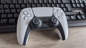 A PS5 controller sitting on top of a keyboard.