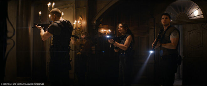 Left to right: Tom Hopper as Albert Wesker, Chad Rook as Richard Aiken, Hannah John-Kamen as Jill Valentine and Robbie Amell as Chris Redfield, exploring the mansion with guns and flashlights in the film Resident Evil: Welcome To Raccoon City