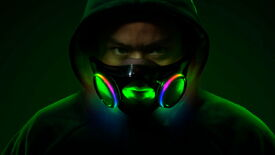 A man in a hood wearing Razer's Project Hazel face mask, and his face is illuminated by its interior RGB lighting