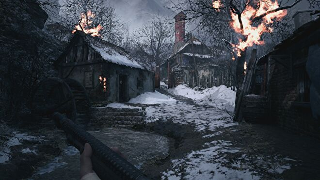 A burning house and tree near a river in Resident Evil Village with ray tracing switched on