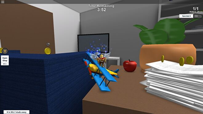 A winged Roblox character traverses a giant living room by jumping on a toy aeroplane on a table.
