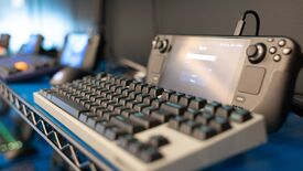 A Steam Deck dev kit stands upright, in front of a mechanical keyboard.