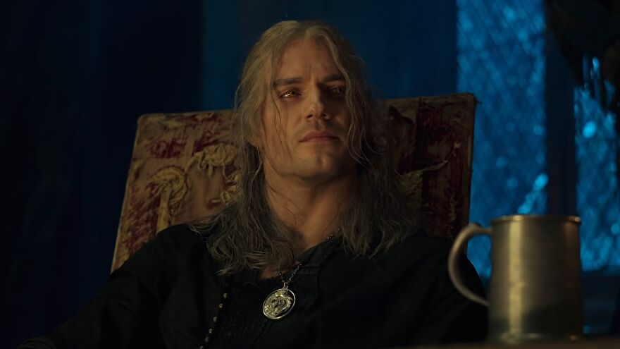 Netflix's The Witcher series season 2 - Geralt sits in an upholstered chair at night in kaer morhen next to a mug, wearing his Witcher medallion.