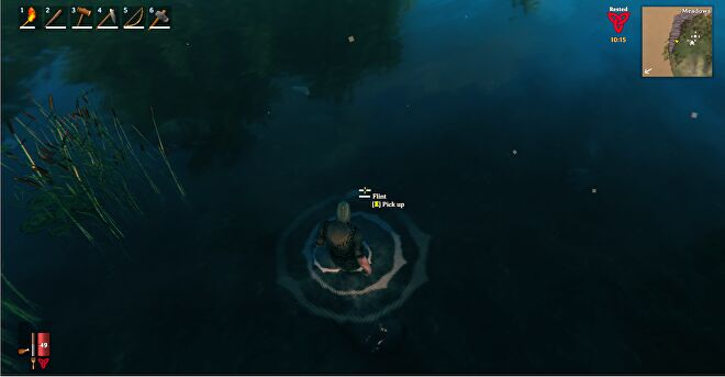 A Valheim screenshot of the player wading into the water to retrieve a piece of Flint on the sea bed.