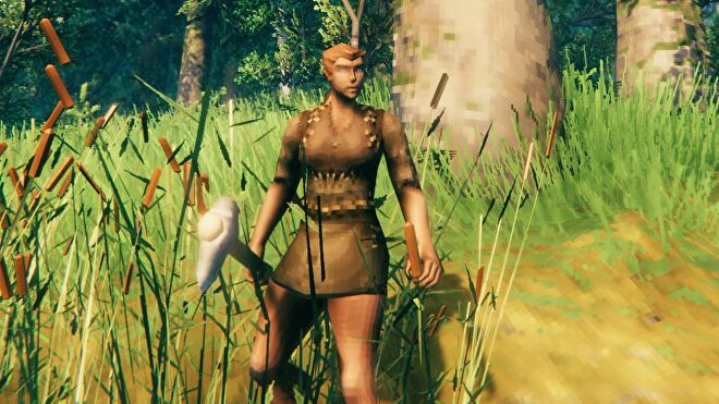A close up of a Viking in Valheim. She is still wearing rags, and is holding an axe.