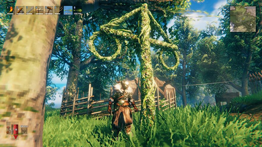 Valheim - A player in armor standing next to a maypole covered in greenery inside a small village.