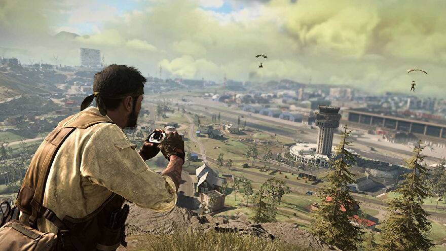 A screenshot of Woods staring out at 1980s Verdansk, binoculars in hand. Two players parachute into Airport in the distance.