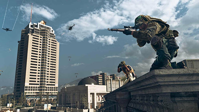 Two players in Warzone on a rooftop scouting for enemies.