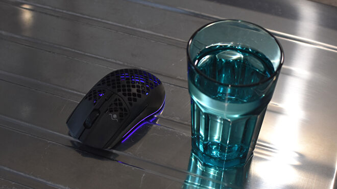 A SteelSeries Aerox 3 Wireless mouse sat next to a glass of water.