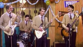 Weezer in the music video to Buddy Holly.